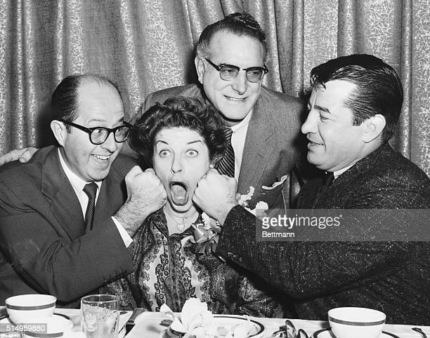 Getting the punchline...New York: Comedienne Martha Raye is amiably punched on the cheeks by comedy star Phil Silvers and former middleweight boxing...