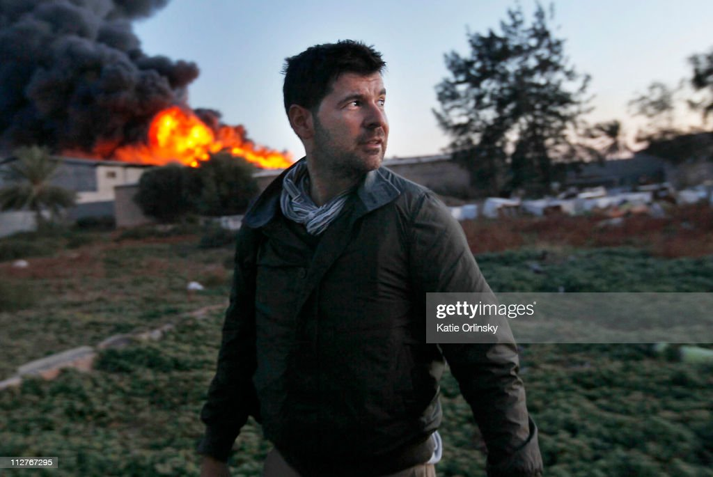 Getty Images photographer Chris Hondros stands in front of a burning building while on assignment on April 18, 2011, in Misrata, Libya. Hondros, who was on assignment in Misrata, Libya, was killed on April 20, 2011 by a rocket-propelled grenade (RPG).