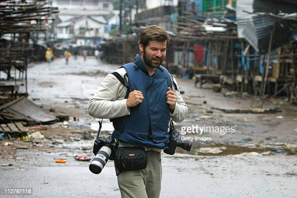 Getty Images photographer Chris Hondros walks through the streets on August 3 in Monrovia Liberia Hondros who was on assignment in Misrata Libya was...