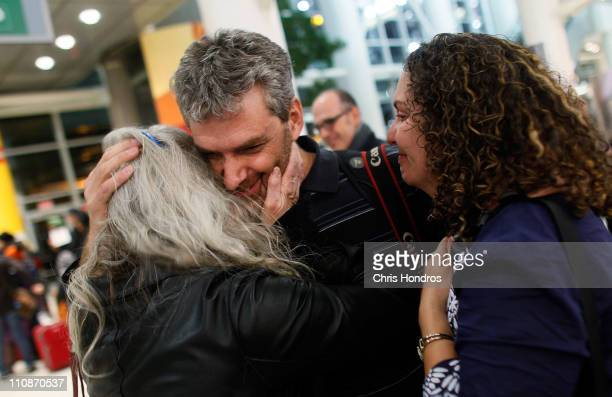 Getty Images photographer Joe Raedle hugs his mother while wife Nancy San Martin watches after arriving to New York following his release from...
