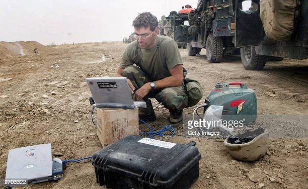 Getty Images staff photographer Joe Raedle transmits images to the picture desk by satellite telephone April 12 2003 from the road to Al Kut Iraq He...