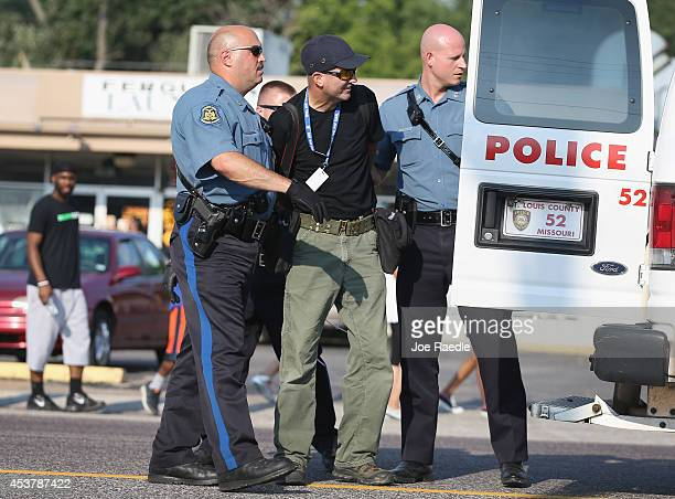 Getty Images staff photographer Scott Olson is placed into a paddy wagon after being arrested by police as he covers the demonstration following the...