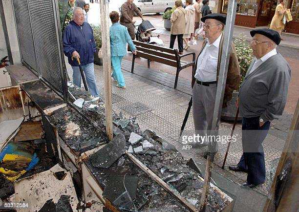 Unidentified men observe a voyages establishment attacked last night by unidentified hooded people 01 August 2005 in Madrid More than ten...