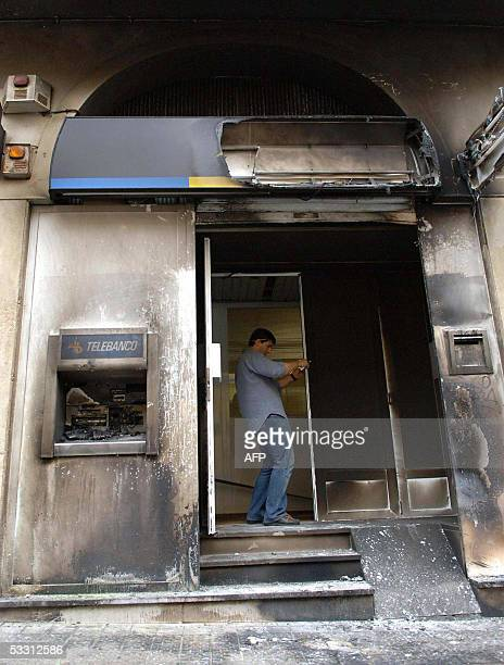 Unidentified men works at a door of a bank attacked last night by unidentified hooded people 01 August 2005 in Madrid More than ten establishments...