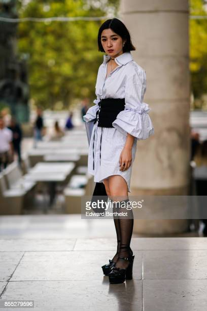 A geust wears a white dress a black corset high tights outside the Lemaire show during Paris Fashion Week Womenswear Spring/Summer 2018 on September...