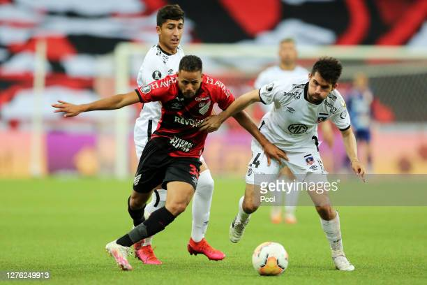 Geuvanio of Athletico Paranaense fights for the ball with Cesar Fuentes of ColoColo during a group C match of Copa CONMEBOL Libertadores 2020 between...