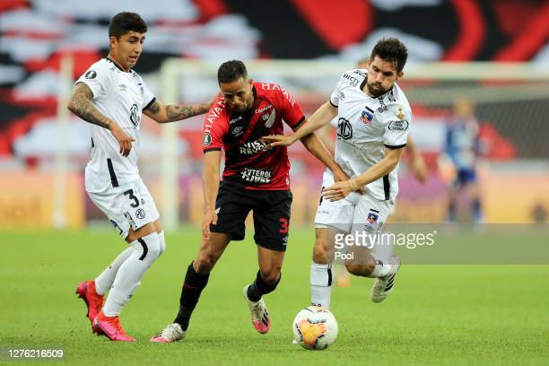 Geuvanio of Athletico Paranaense fights for the ball with Pablo Soto and Cesar Fuentes of ColoColo during a group C match of Copa CONMEBOL...