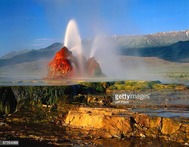 geysers spew water near snowcapped mountains. black rock desert-high rock canyon emigrant trails national conservation area, nevada. - great basin stock pictures, royalty-free photos & images