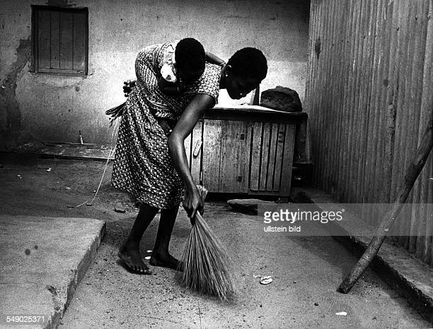 A young girl cleaning the court yard of her house with a baby sister on her back