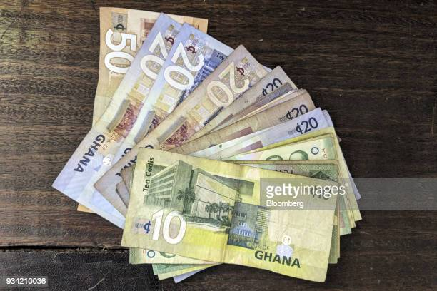 Ghana cedi banknotes sit arranged on a table in Accra Ghana on Thursday March 15 2018 Ghana wants to shake up the way it collects tax with the...