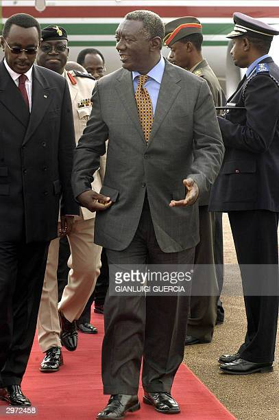 Ghana President John Kufor arrives 12 February 2004 at Kigali International Airport to attend the NEPAD Summit and is received on his arrival by...