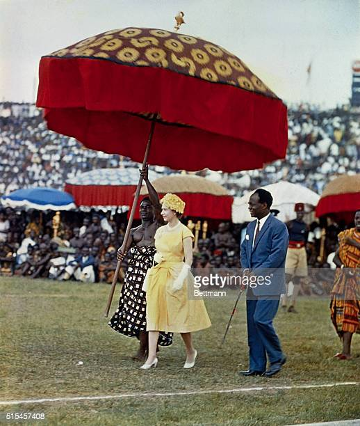 Queen Elizabeth II makes her way underneath a large gaily colored umbrella to a dais to watch the Durbar of the Ashanti Chiefs at Kumasi Sports...