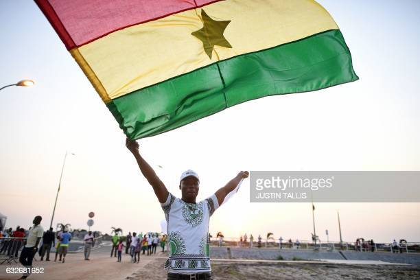 A Ghana supporter waves a Ghanaian flag as he arrives to attend the 2017 Africa Cup of Nations group D football match between Egypt and Ghana in...
