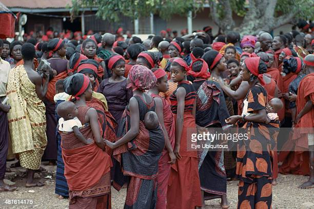 Ghana, Tribal People, Group of women carrying babies on their backs at Ashanti funeral, dressed in red the color of mourning. Large mixed crowd in...