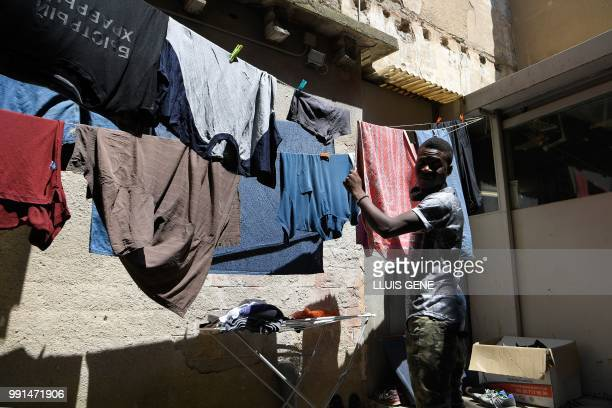 Ghanaian Ahmed Musa tends his laundered clothes at the abandoned school of La Massana in the center of Barcelona on July 3 occupied since midApril by...