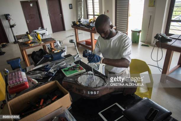 Ghanaian artist Joseph AwuahDarko works on a clock the pieces of which were found at Agbogloshie dumpsite at his workshop at Ashesi University...