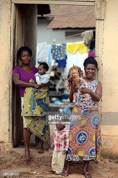 Ghanaian family stand in front of their house on October 132013 in Accra Ghana Unlike other African countries Ghana tends to be more secure and a...