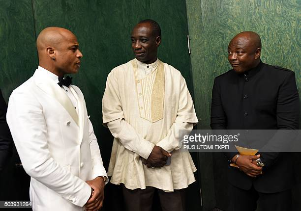 Ghanaian football legend Abedi Pele Ayew speaks with the country's High Commissioner to Nigeria William AwinadoeKanyrige and son Andre Anyew before...