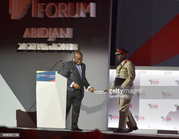 Ghanaian President Nana AkufoAddo delivers a speech as his aidedecamp gives him his speech during the opening session of the AFRICA CEO FORUM in...