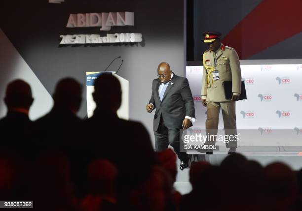 Ghanaian President Nana AkufoAddo leaves the podium with his aidedecamp after delivering his speech during the opening session of the AFRICA CEO...