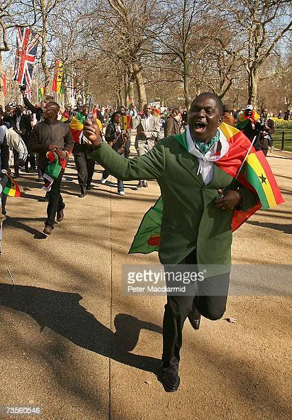 Ghanaian runs after a coach carrying Queen Elizabeth II and President John Kufuor of Ghana on The Mall on March 13 2007 in London England The...