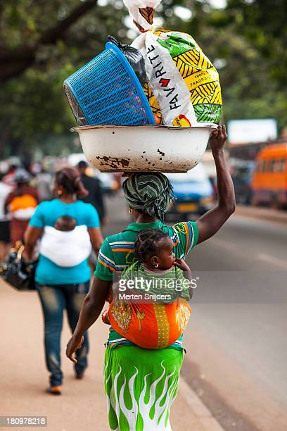 ghanaian woman with small cargo and child - merten snijders stockfoto's en -beelden