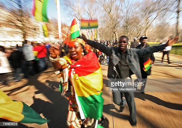 Ghanaians run after a coach carrying Queen Elizabeth II and President John Kufuor of Ghana on The Mall on March 13 2007 in London England The...