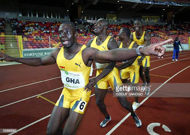 Ghanains Christian Nsiah Eric Nkansah Miles Myles and Gad Boake take a victory lap 13 October 2003 at the stadium in Abuja after winning the 4x100...