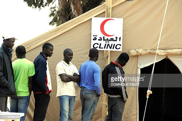 Ghanan refugees who fled Libya line up at the Clinic of the United Arab United refugee camp near the Tunisian border town of Ras Jdir on March 14...