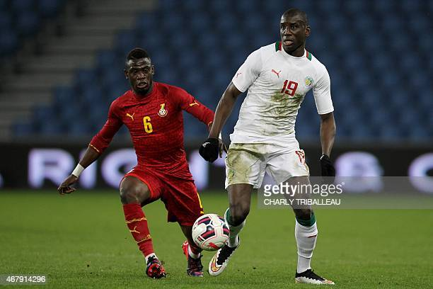 Ghana's Afriyea Acquah vies for the ball with Senegal's Demba Ba during the International Friendly football match between Senegal and Ghana on March...