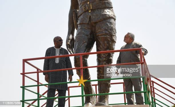 TOPSHOT Ghana's former President Jerry Rawlings and Burkina Faso's President Roch Marc Christian Kabore poses under the bronze statue of Burkina...