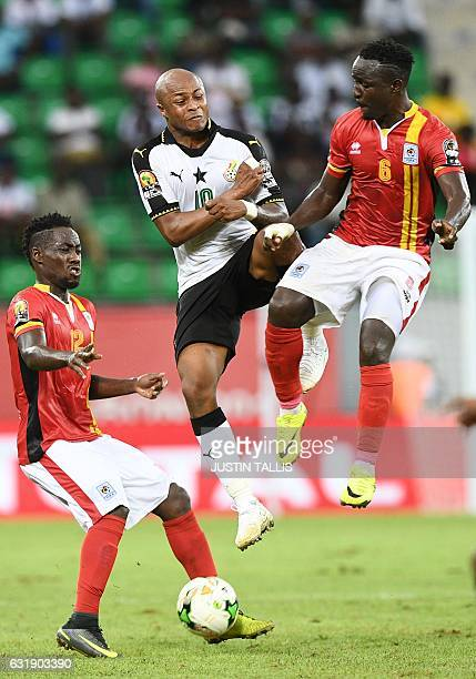 Ghana's forward Andre Ayew challenges Uganda's midfielder Tony Mawejje and Uganda's defender Denis Iguma during the 2017 Africa Cup of Nations group...