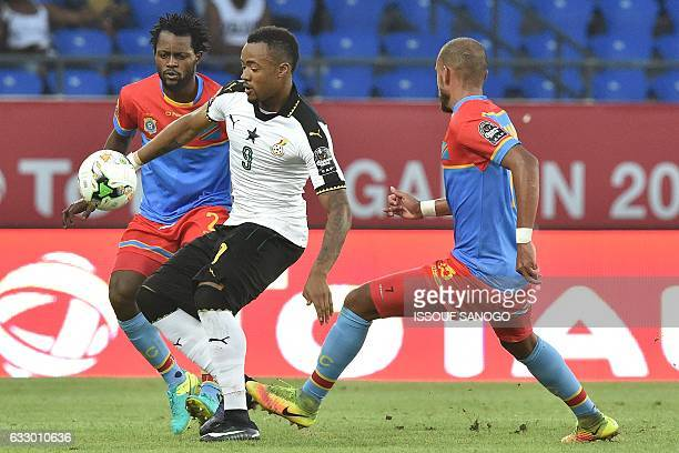 Ghana's forward Jordan Ayew challenges Democratic Republic of the Congo's defender Issama Mpeko and Democratic Republic of the Congo's midfielder...