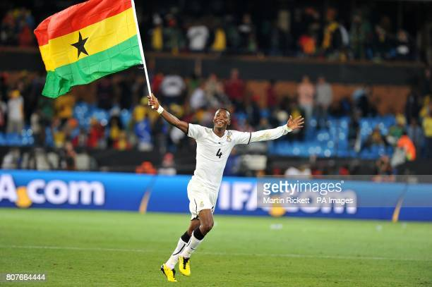 Ghana's John Pantsil celebrates with a Ghanaian flag after the final whistle