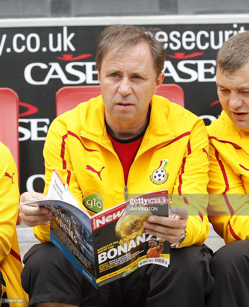 Ghana's national football team head coach Milovan Rajevac (C) looks at a magazine before kick off of a friendly match against the Latvian national team at the Stadiummk in Milton Keynes, central England, on June 5, 2010. AFP PHOTO/Ian Kington
