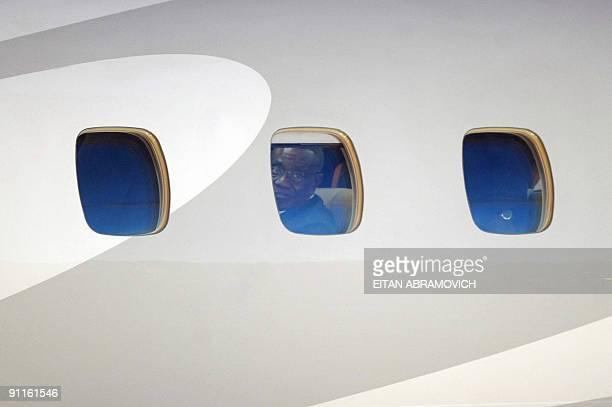 Ghana's President Jhon Atta Mills peers from the porthole of the plane upon arrival in Margarita Island Nueva Esparta state northwestern Venezuela on...