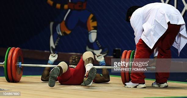Ghana's Seth Degbe Fetrie is helped by a volunteer after his failed attempt to lift during the men's 69 kg weightlifting clean and jerk event during...