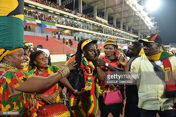 A Ghana's supporter holds her face at the end of the 2015 African Cup of Nations semifinal football match between Equatorial Guinea and Ghana in...