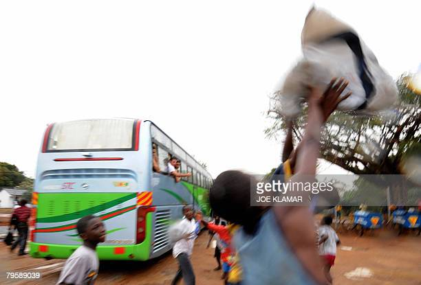 Ghanian boys scuffle over a shirt thrown from the bus by Egyptian goalkeeper Mohamed Abdel Monsef after Egypt's team practice in Kumasi on February...