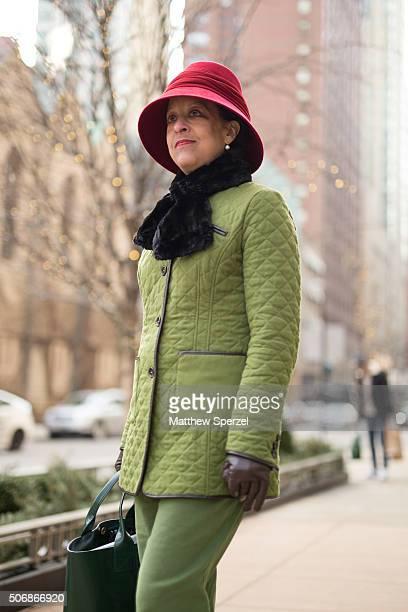 Ghenete Zelleke is seen on Michigan Avenue wearing a red custommade felt hat black faux fur scarf leaf green wool with leather trim Schneiders coat...