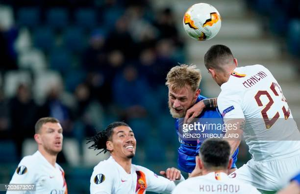 Ghent's Ukrainian defender Igor Plastun heads the ball with AS Roma's Italian defender Gianluca Mancini during the UEFA Europa League round of 32...