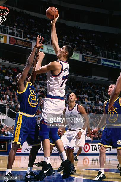Gheorge Muresan of the Washington Bullets shoots the ball against Joe Smith of the Golden State Warriors circa 1997 at the OaklandAlameda County...