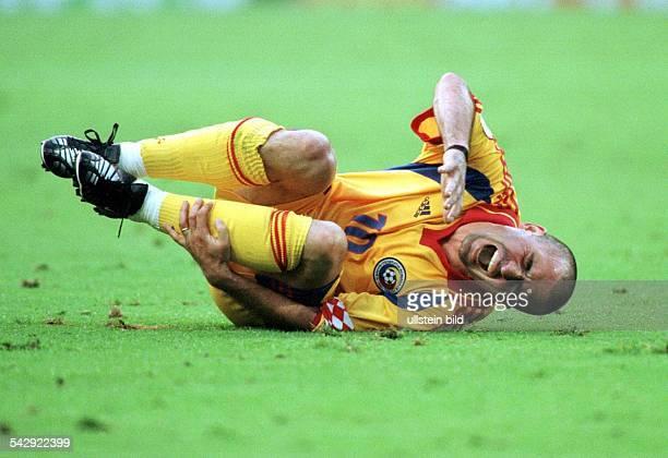 Gheorghe Hagi Mittelfeldspieler der rumänischen Nationalmannschaft krümmt sich während der FußballEuropameisterschaft 2000 vor Schmerz am Boden und...