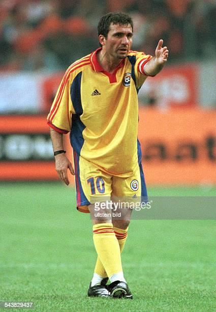 Gheorghe Hagi Mittelfeldspieler der rumänischen FußballNationalmannschaft zeigt mit ausgestrecktem linken Arm nach vorn Hagi trägt die Kapitänsbinde...