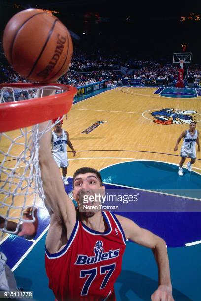 Gheorghe Muresan of the Washington Bullets dunks during a game played on March 13, 1995 at the Charlotte Coliseum in Charlotte, North Carolina. NOTE...