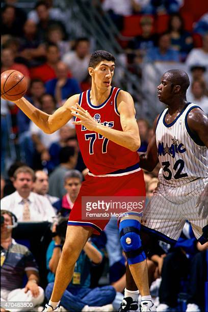 Gheorghe Muresan of the Washington Bullets handles the ball against Shaquille O'Neal of the Orlando Magic on October 15 1994 at the Amway Arena in...