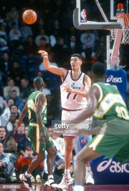 Gheorghe Muresan of the Washington Bullets passes the ball over the top of Gary Payton of the Seattle Supersonics during an NBA basketball game circa...