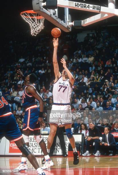 Gheorghe Muresan of the Washington Bullets shoots over Patrick Ewing of the New York Knicks during an NBA basketball game circa 1995 at the US...