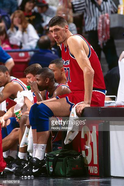 Gheorghe Muresan of the Washington Bullets sits on the scorers table during a game played on March 3 1996 at Arco Arena in Sacramento California NOTE...