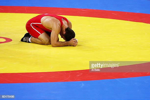 Gheorghita Stefan of Romania lays on the mat after losing in the semilfinals of the 74kg Men's Freestyle wrestling event at the China Agriculture...